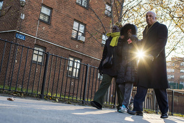 "Assemblyman Barron, his wife City Councilwoman Barron and area resident Butler walk past the building in a public housing project in Brooklyn known as the ""Pink Houses"" where Gurley was killed by what the NYPD is"