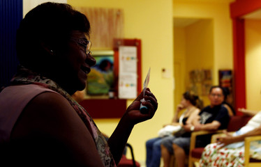 Paula holds a membership card to the DC Health Care Alliance, as she is interviewed near the waiting room of the La Clinica Del Pueblo community health clinic in Washington