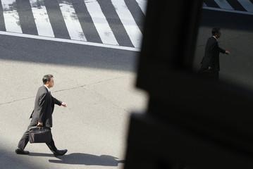 A reflection of a man crossing a street is seen on a window in Tokyo