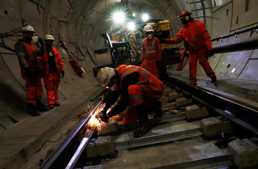 Workers lay railway track in a tunnel of the Crossrail project in Stepney, east London