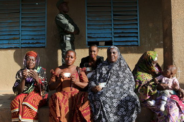 Women show their voting cards at a polling station during the presidential and legislative election in Ouagadougou
