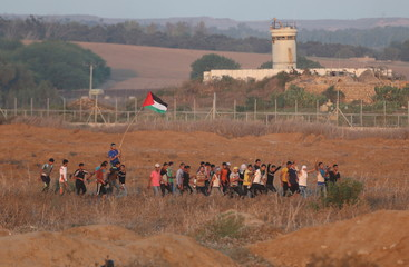 Palestinian protesters take part in a protest as they make their way to clashes with Israeli troops near the border between Israel and Central Gaza Strip