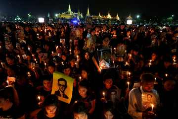 Mourners hold up pictures of Thailand's late King Bhumibol Adulyadej and candle lights as they gather with others during a vigil to mark his birthday outside the Grand Palace in Bangkok