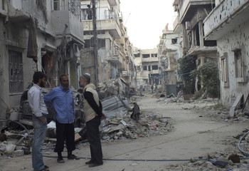 Men chat as they stand in front of buildings damaged by what activists said was shelling by forces loyal to Syria's President Bashar al-Assad in the besieged area of Homs