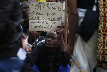 A mineworkers holds up a sign during a march at Lonmin's Marikana mine in South Africa's North West Province