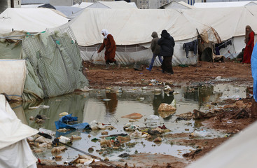 Syrian refugees walk near a puddle of rain outside tents at the Bab Al-Salam refugee camp in Azaz