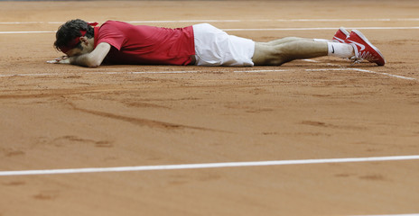 Switzerland's Roger Federer reacts on the clay court after winning his Davis Cup final singles tennis match against France's Richard Gasquet at the Pierre-Mauroy stadium in Villeneuve d'Ascq