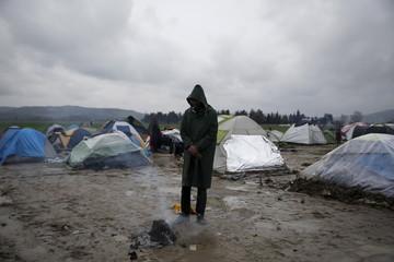 A migrant warms himself next to a bonfire at a makeshift camp at the Greek-Macedonian border, near the village of Idomeni