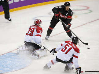 Canada's Crosby sets up a play that resulted in a goal by teammate Carter against Austria's goalie Starkbaum and Austria's Trattnig during the second period of their