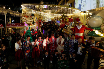 Models pose outside Harbour City shopping mall during a Christmas lights illuminating ceremony in Hong Kong