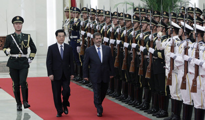 China's President Hu and Egyptian counterpart Mursi inspect honour guards during welcoming ceremony in Beijing