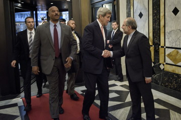 U.S. Secretary of State John Kerry (C) is greeted by Iran's Foreign Minister Javad Zarif's chief of staff (R) before a meeting in Vienna, Austria