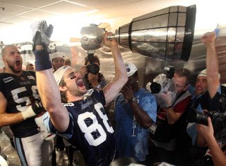 Toronto Argonauts' Mike Bradwell celebrates with the Grey Cup after his team defeated the Calgary Stampeders in the 100th CFL Grey Cup championship football game in Toronto