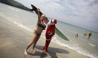 "Carlos Bahia, dressed as Santa Claus, poses for a ""selfie"" with a woman at the Maresias beach, in the state of Sao Paulo"