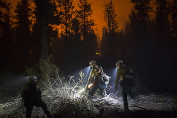 Members of El Carrizo Hot Shots crew cut a line through the night to try to contain the Lake Fire in the San Bernardino National Forest, California