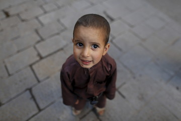 Boy reacts to the camera as he plays on a street in the old quarter of Yemen's capital Sanaa