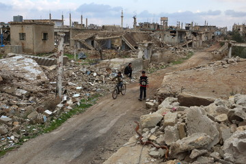 A boy rides a bicycle past a man sitting on rubble of a damaged house in the rebel held historic southern town of Bosra al-Sham, Deraa