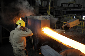 A worker processes a red hot steel bar inside a foundry of a steel factory in Concepcion city