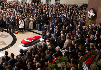 Friends and relatives gather around the flag-wrapped coffin of court employee Musa Can during a ceremony at the courthouse in Izmir