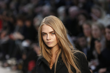 Model Cara Delevingne presents a creation from the Burberry Prorsum Autumn/Winter 2013 collection during London Fashion Week
