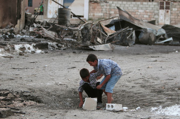 Boys play in a crater caused by an air strike in the northeastern city of Hasaka