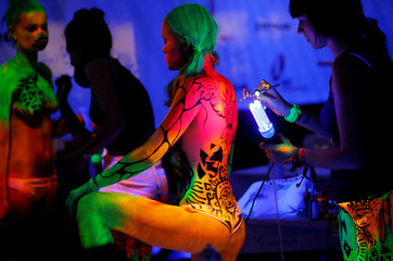 Artist use ultraviolet light paint on models during the World Bodypainting Festival in Poertschach