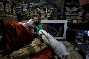 "Former lawyer from Moscow who is called ""Russian hobbit"" Alekseyev looks at rabbit named Petrushka at his underground home in forest on side of road northeast from Moscow"