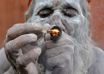 A Hindu ascetic smokes marijuana outside the Bhavnath temple during the Mahashivratri festival in Gujarat