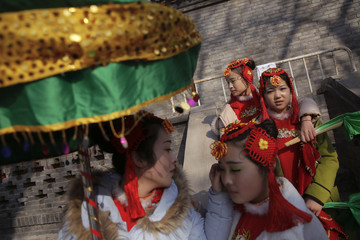 A girl helps the other one with make-up as performers wait for their turn to go onto the stage at the Longtan park as the Chinese Lunar New Year is celebrated in Beijing