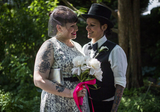"""May (R) and Michelle Brand pose for a picture before """"The Celebration of Love"""", a grand wedding where over 100 LGBT couples got married, at Casa Loma in Toronto"""