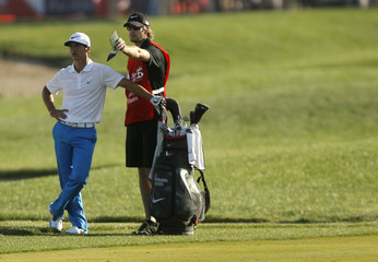 Olesen of Denmark speaks to his caddie at the 18th hole during the third round of the Abu Dhabi Golf Championship at the Abu Dhabi Golf Club