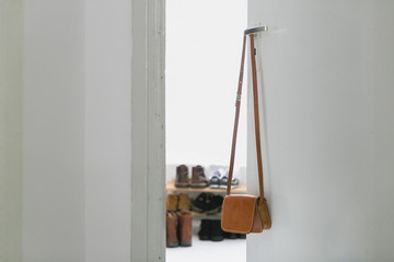 a small leather purse hangs on a door handle
