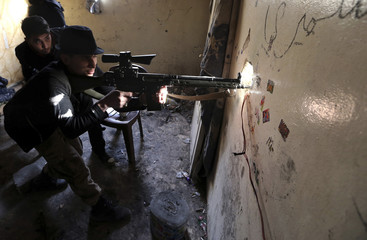 A Free Syrian Army fighter aims his rifle before opening fire at Syrian Army soldiers in the Arabeen neighbourhood of Damascus