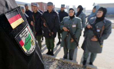 The emblem patch of a German police instructor is pictured in front of female and male Afghan National Police (ANP) officers before a drill at a training centre near the German Bundeswehr army camp