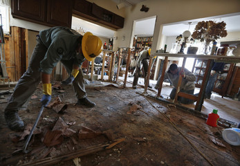 Members of the Southwest Conservation Corp. help a local contractor clean out a damaged home in the aftermath of Hurricane Sandy, in the Breezy Point area of New York