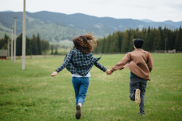 Couple of lovers holding hands and running away in mountains. Woman and man in love walking outdoors.