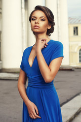 Fashion style portrait. Young elegant woman in blue long flying dress posing at stairway against old city building