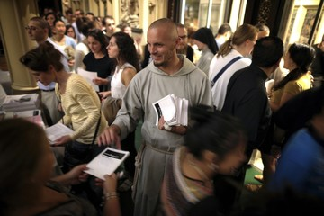 A Franciscan Friar greets attendees during the Eucharistic adoration ceremony during The Catholic Underground event at The Church of Our Lady of Good Counsel in New York,