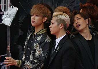 Members of the South Korean K-Pop band GOT7 react in front of an official camera on the red carpet during 2015 Mnet Asian Music Awards (MAMA) in Hong Kong