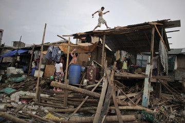 A man make repairs to his house which was severely damaged by Typhoons Nesat and Nalgae at a fishing village in Navotas