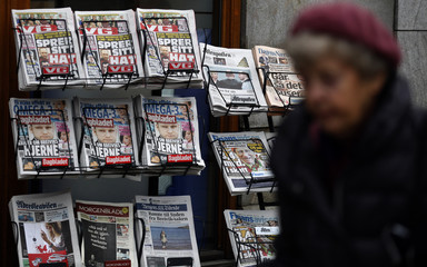 Woman walks past Norwegian newspapers with front page features of defendant Norwegian mass killer Anders Behring Breivik in Oslo