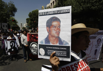 Relatives and activists hold photographs of people who disappeared in Mexico's drug violence during protest in Mexico City