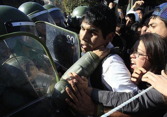 Riot policemen try to arrest students as they shout slogans against Chile's government near Copiapo city