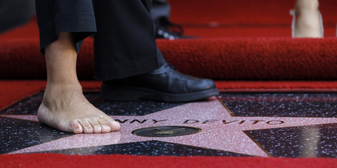 DeVito poses on his star without a shoe and sock after it was unveiled on the Walk of Fame in Hollywood