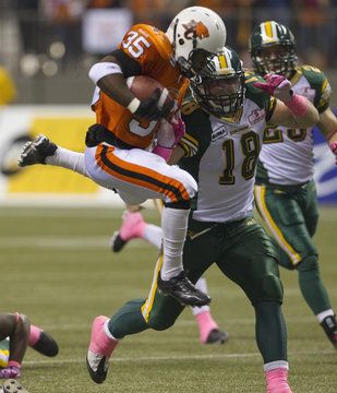 BC Lions' Brown is chased by Edmonton Eskimos' Darcy Brown during CFL football game in Vancouver