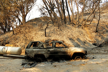 A destroyed vehicle sits on a property that was heavily damaged after the Soberanes Fire burned through the Palo Colorado area, north of Big Sur, California