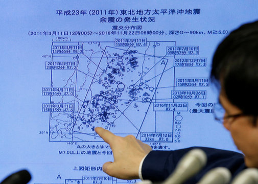 Japan Meteorological Agency's earthquake and volcano observations division director Koji Nakamura points at a map showing earthquake information during a news conference in Tokyo