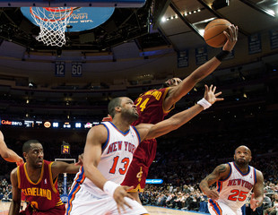 Cleveland Cavaliers' Samuels reaches for a rebound over New York Knicks' Williams and Carter in the fourth quarter of their NBA basketball game in New York