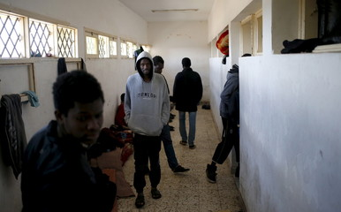 Illegal migrants stand in an immigration holding centre located on the outskirts of Misrata