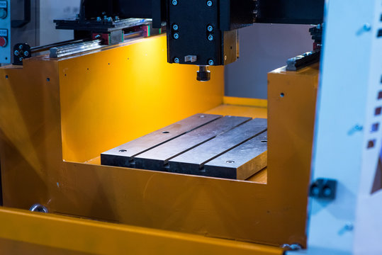Close-up of the wire - EDM CNC machine while cutting the sample work pieces in light blue tone and lighting effect